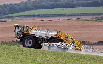 A Lite-Trac four-wheeled self-propelled crop sprayer spraying pesticide on a field (photo credit: Lite-Trac/Wikipedia Commons)
