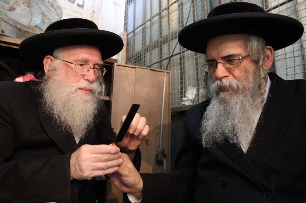 Ultra-Orthodox Jewish men examine knives used for slaughtering chickens (photo credit: Nati Shohat/Flash90/File)