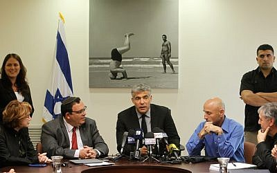 Yair Lapid, center, at a meeting of his Yesh Atid Knesset faction. (photo credit: Miriam Alster/Flash90)