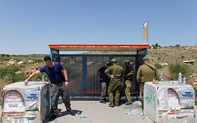 Israeli security forces at a bus stop at the Tapuah Junction inspect the site of a terror attack on April 30, 2013 (photo credit: Flash90)
