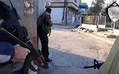 Syrian rebels taking cover during fighting against government forces. (photo credit: AP/Local Council of Barzeh)