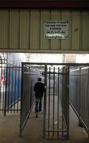 A Palestinian man walks through the Qalandiya checkpoint, April 30 (photo credit: Elhanan Miller/Times of Israel)