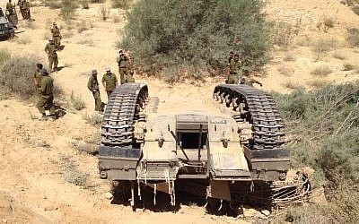 Soldiers examine a tank after it flipped during a training accident, Tuesday (photo credit: Alon Chasid)