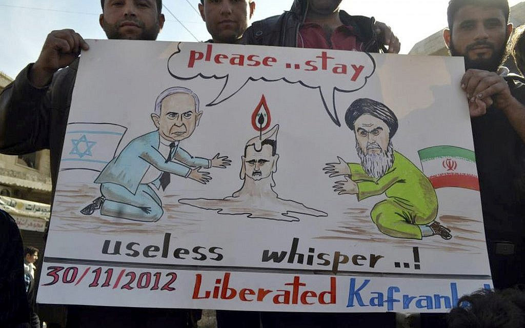 Anti-Assad protesters hold up a caricature placard representing Iranian supreme leader Ayatollah Ali Khamenei, right, and Israeli Prime Minister Benjamin Netanyahu, left, during a demonstration at Kfar Nebel near Idlib, Friday, Nov. 30, 2012 (photo credit: AP/ENN)