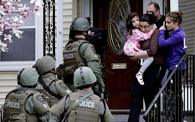 Illustrative image: A woman carries a girl from their home as a SWAT team searching for a suspect in the Boston Marathon bombings enters the building in Watertown, Mass., Friday, April 19, 2013. (photo credit: AP Photo/Charles Krupa)