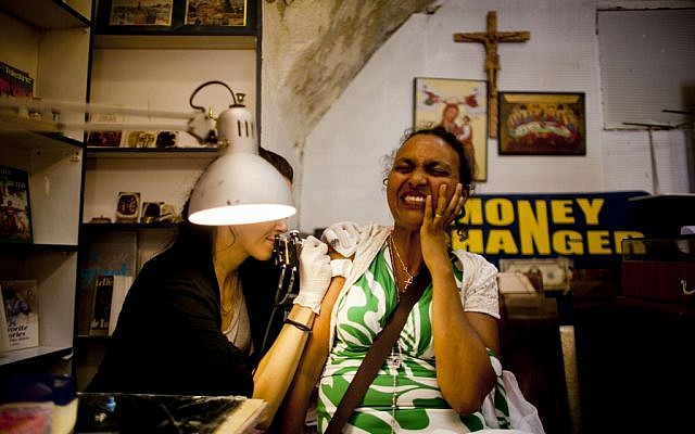 Etetu Legesse, a Christian Orthodox pilgrim from Ethiopia, reacts as she receives a tattoo in a shop owned by the Razzouk family in Jerusalem. (photo credit: AP/Dusan Vranic)