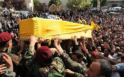 Hezbollah fighters in military uniform carry the coffin of one of their own, Hassan Faisal Shuker, 18, who was killed in a battle against Syrian rebels in the town of Qusair, Syria, in May, 2013 (photo credit: AP)