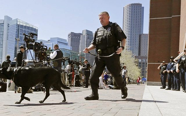 A Department of Homeland Security police officer patrols with his dog outside the Moakley Federal Courthouse in Boston in May 2013, following the marathon bombings. (photo credit: AP/Charles Krupa)