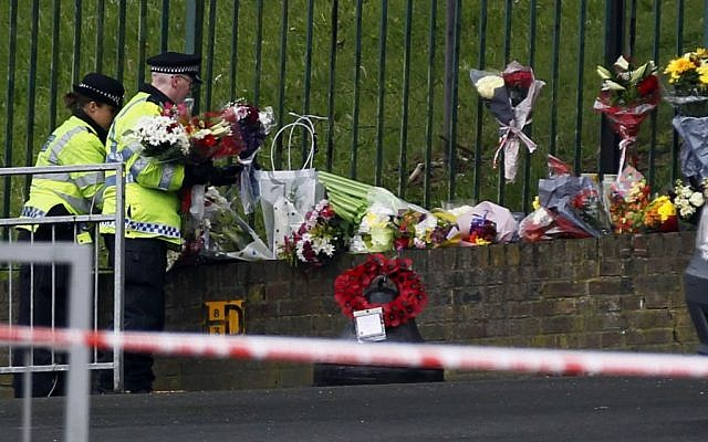 Police officers lay down floral tributes handed to them by members of the public Thursday at the scene of the terror attack in Woolwich, southeast London, a day earlier. (photo credit: AP/Sang Tan)