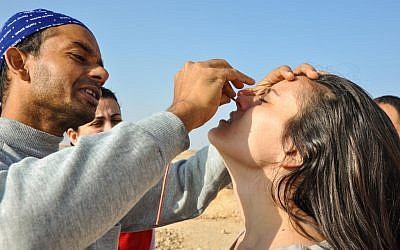 Swadesh Sharma helps Samantha place the small tube through her nostril. The kriya cleans out excess build up that accumulates in the nasal passage. (photo credit: Michal Shmulovich)