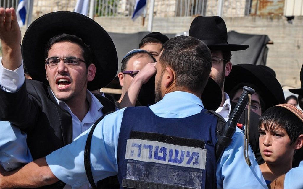 Police keep ultra-Orthodox teens from disturbing a Women of the Wall prayer service in May. (photo credit: Michal Shmulovich/Times of Israel)