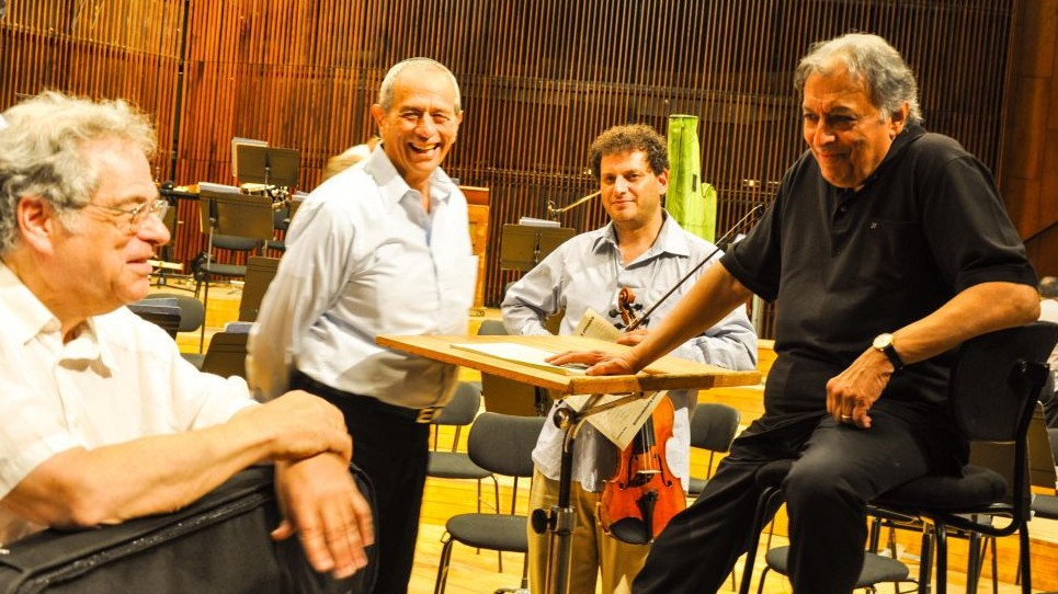 Zubin Mehta, right, the music director of the Israel Philharmonic Orchestra, chats with violinst Itzhak Perlman after their dress rehearsal Friday (photo credit: Michal Shmulovich/Times of Israel)