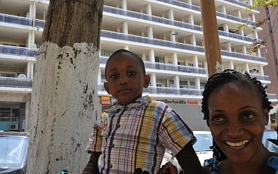 A Senegalese mother and her son standing outside the Israeli Embassy in Dakar, April 2013. (photo credit: Cnaan Liphshiz/JTA)