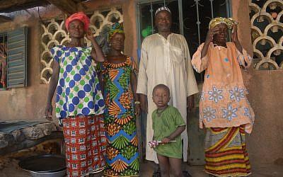 Dougoutigo Fadiga, president of Bani Israel, outside his Senegal home with his three wives and one of his sons, May 2013. (photo credit: Cnaan Liphshiz/JTA)