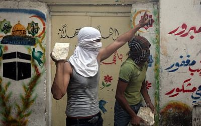 A Palestinian youth prepares to throw a stone at Israeli policemen near Jerusalem's Lion Gate, October 2009 (photo credit: Yossi Zamir/Flash90)