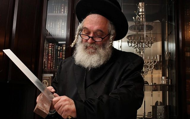 A rabbi sharpens the knife to be used for traditional Jewish slaughter (illustrative photo credit: Kobi Gideon/Flash90)
