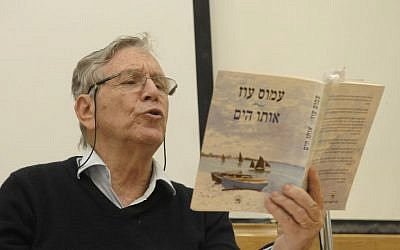 Renowned Israeli author Amos Oz reads from one of his books in Tel Aviv. (photo credit: Tomer Neuberg/Flash90)