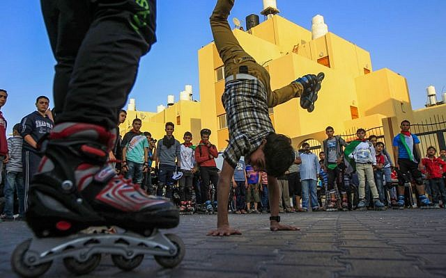 Time will tell if this is manly enough behavior. A Palestinian youth with skates on his feet stands on his hands in the southern Gaza town of Rafah during a rally for solidarity with Palestinian prisoners in April 2013. (photo credit: Abed Rahim Khatib/Flash90).