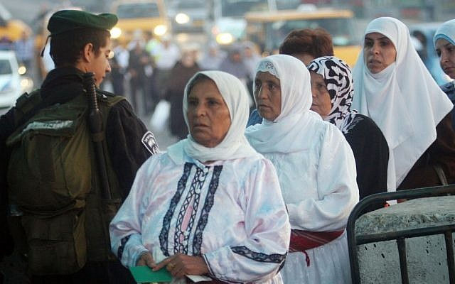Israeli border police officers check documents of Palestinian women who wait to cross the Qalandia checkpoint on the outskirts of the West Bank city of Ramallah. photo credit: (Issam Rimawi/Flash90)