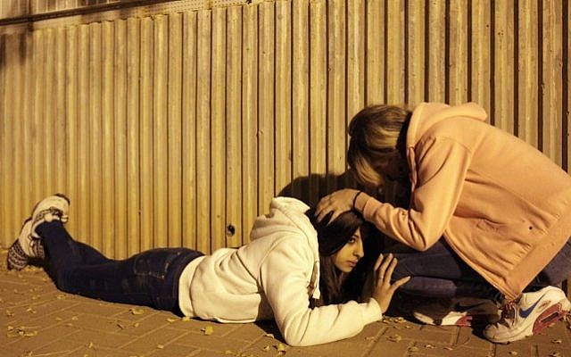 Illustrative: Young Israeli women take cover as a siren sounds warning of incoming rockets fired from Gaza, November 21, 2012. (Edi Israel/FLASH90)
