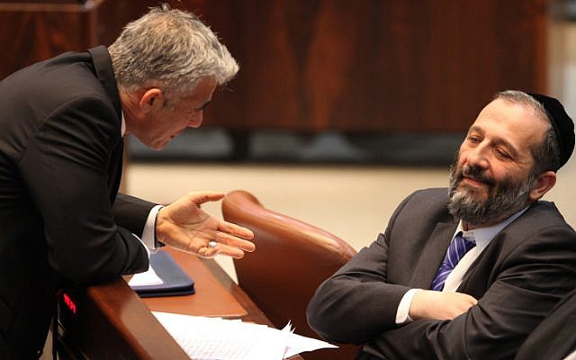 Then-finance minister Yair Lapid, left, talks to Shas chairman Aryeh Deri at the Knesset in March 2013. (Isaac Harari/Flash90)