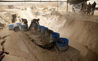 Palestinian workers unload gravel being pulled from a smuggling tunnel between the Hamas-ruled Gaza Strip and Egypt in the southern Gaza Strip city of Rafah on April 3, 2013 (photo credit: Wissam Nassar/Flash90)