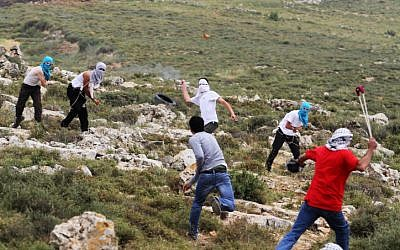 Illustrative photo: Masked Jewish settlers, background, and Palestinians, foreground, hurl stones during clashes in the West Bank, Friday, May 3, 2013. (Issam Rimawi/Flash90)