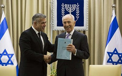 Finance Minister Yair Lapid delivers a copy of the 2013 budget to President Shimon Peres in Jerusalem, Thursday, May 9, 2013 (photo credit: Yonatan Sindel/Flash90)