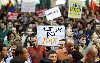 Israelis hold up signs as they take part in a protest march against Finance Minister Yair Lapid's proposed budget cuts and tax hikes, in Tel Aviv on Saturday, May 11, 2013.  (photo credit: Flash90)