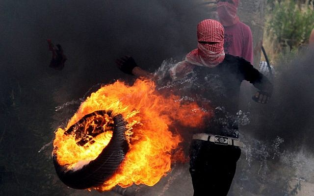 A Palestinian sets fire to a tire during clashes between Palestinians and Israeli soldiers outside the Ofer prison after a march marking the 65th anniversary of the Nakba, or 'Day of Catastrophe,' on Wednesday. (photo credit: Issam Rimawi/Flash90)
