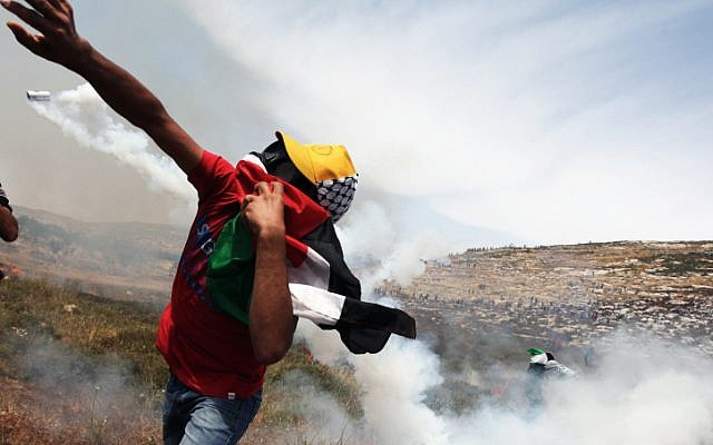 Palestinian hurls rocks at Israeli security forces during clashes near Ramallah on Friday, May 17 (photo credit: Issam Rimawi/Flash90)