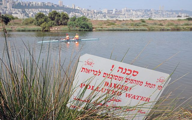 Illustrative photo of Israeli rowers cruise past a sign warning of polluted water outside Haifa on May 18, 2013. (photo credit: Shay Levy/Flash 90)