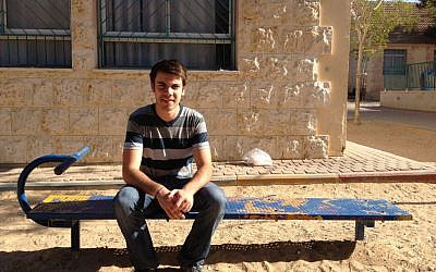 "Alexander Gould, who played Shane Botwin in ""Weeds,"" sitting in the playground of the Yeruham elementary school where he taught English this spring (photo credit: Jessica Steinberg/Times of Israel)"