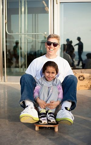 Michael Brooke, the founder of Longboarding for Peace, with a young enthusiast at the Peres Center for Peace in Jaffa (photo credi: Yohav Trudler)