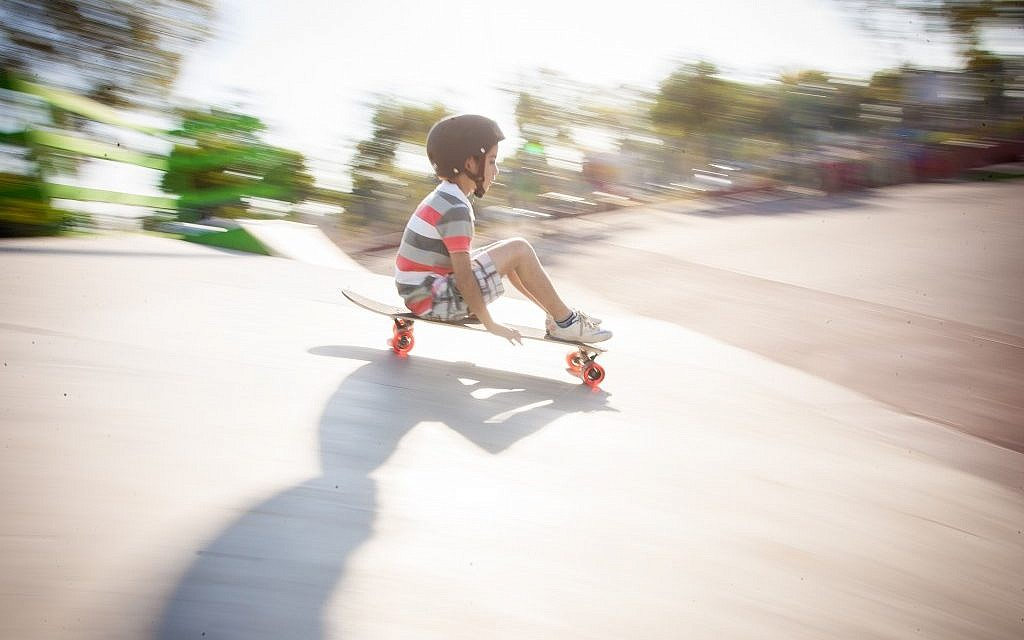 A boy from Sderot feels the wind in his face as he glides on a longboard (photo credit: Yair Hasidof)