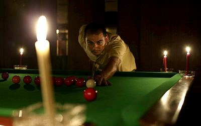 An Egyptian man plays snooker by candlelight at a club in the Mohandessin district, in Giza, Egypt, on Saturday, May 25, 2013. (photo credit: AP Photo/Hassan Ammar)
