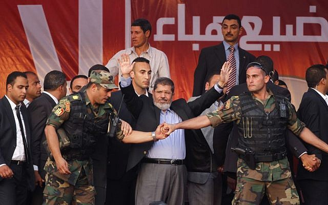 Mohammed Morsi waves to supporters after giving a speech at Tahrir Square in Cairo, on June 29, 2012. (photo credit: AP Photo/Khalil Hamra, File)