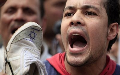 An Egyptian man chants anti-Israeli slogans during a Muslim Brotherhood-staged anti-Israel rally in Cairo on Friday. Meanwhile, a youth activist was detained Friday for 'incitement' a few days after he expressed criticism of Morsi's party via his movement's website (photo credit: Khalil Hamra/AP)