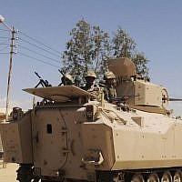 Egyptian army soldiers patrol in an armored vehicle, backed by a helicopter gunship, during a sweep through villages in the northern Sinai Peninsula, Egypt, in May 2013. (AP)