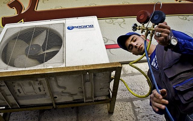 Mohammed Nabouti, a 21-year-old technician, fixes the air conditioner of a shop in Amman, Jordan on Monday, March 4, 2013. Just six months of learning to fix air conditioners changed Nabouti's life.  (AP Photo/Raad Adayleh)