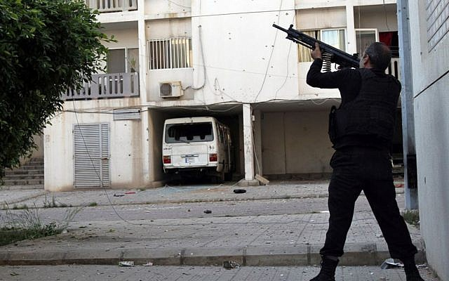 A Sunni gunman fires his machine gun during clashes that erupted between pro and anti-Syrian regime gunmen, in the northern port city of Tripoli, Lebanon, Thursday, May 23, 2013 (photo credit: AP)