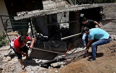 Lebanese men remove debris from their home, which was damaged due to rockets fired by Syrian rebels, according to villagers, in the northeast Lebanese village of Hermel on Wednesday. (photo credit: AP/Hussein Malla)