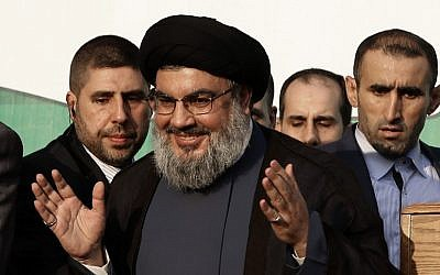 In this Monday, Sept. 17, 2012 file photo, Hezbollah leader Sheik Hassan Nasrallah, center, waves to his supporters, in the southern suburb of Beirut, Lebanon (photo credit: AP/Hussein Malla)
