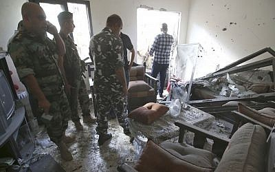Soldiers examine a Beirut home hit by rockets, Sunday (photo credit: Hussein Malla/AP)