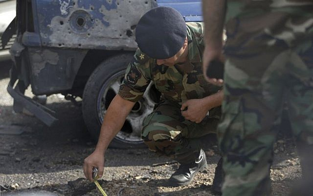 A Lebanese army officer investigates part of a rocket which struck a car exhibit on a street at the Mar Mikhael district, south of Beirut, Lebanon, Sunday May 26, 2013 (photo credit: AP/Hussein Malla)