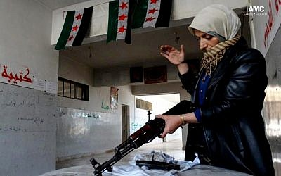 This Tuesday, May 14, 2013 citizen journalism image provided by Aleppo Media Center AMC which has been authenticated based on its contents and other AP reporting, shows the mother of a Syrian rebel cleaning a rifle, in Aleppo, Syria. Activists say Syrian rebels have detonated two car bombs outside the main prison in the northern city of Aleppo and are trying to storm the facility, where hundreds of regime opponents are believed to be held. (Photo credit: AP/Aleppo Media Center AMC)