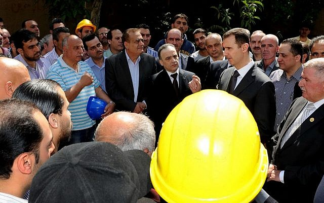 Bashar Assad, center right, visits the Umayyad Electrical Station to mark May Day on Wednesday. (photo credit: AP/SANA)