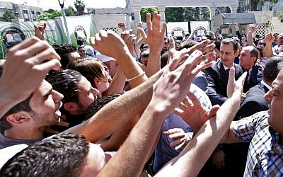 """This photo released on the official Facebook page of Syrian President Bashar Assad, shows Syrian president Bashar Assad, right, surrounded by bodyguards as young people, wave at him during the inauguration ceremony on Saturday of a statue dedicated to """"martyrs"""" from Syrian universities who died in the country's two-year-old uprising and civil war, in Damascus, Syria, Saturday, May. 4, 2013 (photo credit: AP)"""