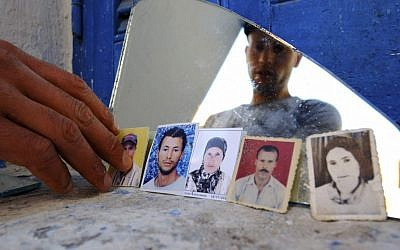 Issam Khedri, 29, eldest brother of cigarette vendor Adel Khedri, shows photos of, from left, his brother Adel, his mother, Latifa, and his father, Habib, in his room in the Mellassine slum of the Tunisian capital, Tunis. Born in Souk al-Jumma, about 150 kilometers west of Tunis, Habib went to the capital as a young man to find work as a day laborer. (AP Photo/Ons Abid)