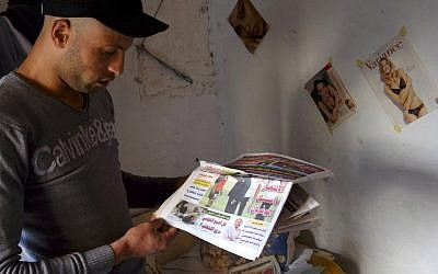Issam Khedri, 29, eldest brother of cigarette vendor Adel Khedri, holds a newspaper with a photo of his brother Adel moments after his self-immolation outside the capital's Municipal Theater, in his room in the Mellassine slum of Tunis, Tunisia. A month after Adel's death, five of the 20 beds at the Ben Arous burn center in Tunis were filled by people who had set themselves on fire. Self-immolations make up about 25 percent of admissions, while the rest are accidents, according to Dr. Amen Allah Messaadi, the center's trauma chief. Some of those setting themselves on fire suffer from mental problems, but most are just like Adel -- unemployed high-school dropouts in their 20s. Such acts are not common among college graduates, he says. (AP Photo/Ons Abid)